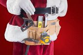 Father Christmas is wearing a tool belt against red background