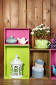 Beautiful colorful shelves with different home related objects on wooden wall background