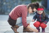 Mother And Daughter Are Painting On The Street.