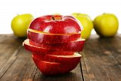 Cut apple on wooden table with other apples background