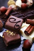 Bars of white and bitter chocolates with candies, hazelnut and cinnamon stick on the dark wooden smooth background with doily