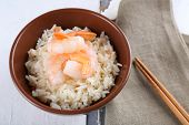 Boiled rice and shrimps in bowl, on wooden background