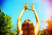 Young woman holding hands in heart shape framing on sky background