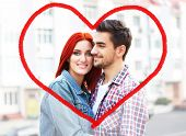 Beautiful young romantic couple and heart-shaped frame on city background