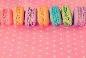 Tasty macaroons on pink polka dot background