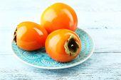 Ripe persimmon on plate, on wooden background