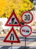 a road construction site is protected by several signs.