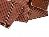 Chopped Chocolate Bar Isolated On White Background. Dark Chocolate Pieces Closeup