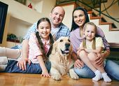Happy family of four and their dog resting at home on weekend