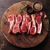 foto of cumin  - Raw fresh lamb ribs with pepper and cumin on wooden cutting board on dark background - JPG
