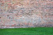 Very old rustic brick wall with grass.