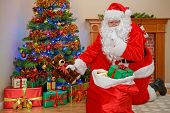 Santa Claus or Father Christmas putting presents under the tree whilst everyone is asleep.