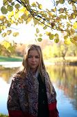 Girl With Her Blond Hair On Background Of Pond And Autumn Trees