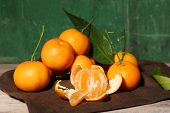 Juicy ripe tangerines with leaves on wooden background