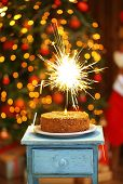 Tasty cake with sparkler on wooden table, on shiny background