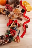 Christmas wreath with materials for decorating on wooden background