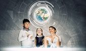 Young teacher and her pupils examining Earth planet. Elements of this image are furnished by NASA
