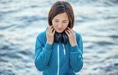 Woman With Headphones On Coast