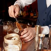 Barman works at bar counter, warm tone, copy space
