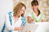 Estudante em casa - duas mulher feliz com Laptop