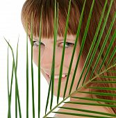 Pretty Female Behind Palm Leaf Over White