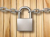 Locked Padlock With Silver Chains Isolated On Wood Background. Safety Concept.