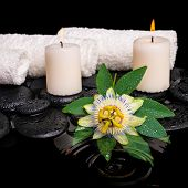 Spa Still Life Of Passiflora Flower, Green Leaf With Drop, Towels And Candles On Zen Stones In Rippl