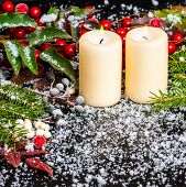 Greeting Christmas Card Of Evergreen Branches, Red Leaves, Berry With Snow And Candles, Closeup