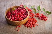 Barberry With Leaves And Dry Goji Berries On Wooden Background