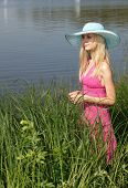 Beautiful blonde in a hat on the riverbank.