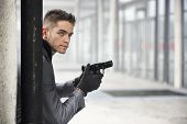 foto of mobsters  - Well dressed handsome young detective or policeman or mobster standing in an urban environment holding a gun with a determined expression coming from behind a column - JPG
