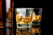 picture of whiskey  - whiskey with ice in glasses near bottle on black background with reflection - JPG