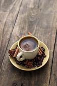 Cup Of Coffee With Cinnamon Sticks On Wood