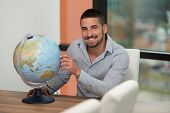 Handsome Young Man Holding A Globe At Office