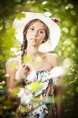 Young beautiful brunette woman wearing a large hat in a sunny day. Portrait of attractive girl