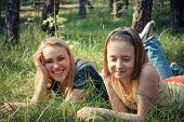 mother and daughter relax in park on grass