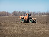 In Field Is Moving An Old Tractor