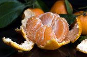 Mandarin Or Tangerine With Leaves And Branches On A Black Marble Table