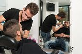 Hairdresser Shaving Man's Chin With A Straight Razor