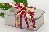Tin box tied with ribbon.