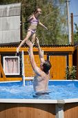 Happy family, active father with little child, adorable toddler girl swim in the pool