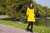 Beautiful woman in yellow coat walking autumn street