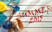 stock photo of spade  - Summer vacation beach items including towel sunglasses and bucket and spade over boards - JPG