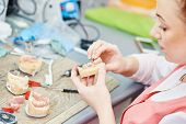 image of false teeth  - Dental technician working with tooth dentures at prosthesis laboratory - JPG
