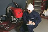 pic of boiler  - A maintenance engineer checking technical data of heating system equipment in a boiler room - JPG