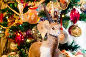 stock photo of ram  - Cute fur ram toy on background with Christmas decorations - JPG