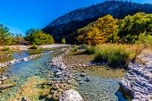 stock photo of crystal clear  - Blue Skies and Bright Beautiful Fall Foliage On The Crystal Clear Rocky Frio River at Garner State Park - JPG