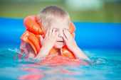 stock photo of pretty-boy  - Pretty little boy in swimming pool - JPG