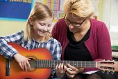 stock photo of pupils  - Teacher Helping Pupil To Play Guitar In Music Lesson - JPG
