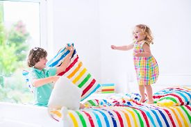 picture of little sister  - Two children happy laughing boy and cute curly haired little girl having fun at pillow fight with feathers in the air jumping laughing and giggling in a white bedroom with colorful bedding. Focus on jumping girl.